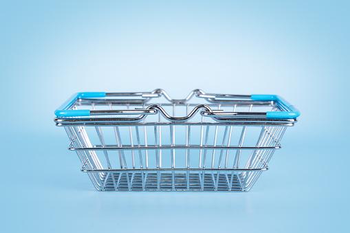 Supermarket shopping basket on light blue background. Empty metal wire basket. Black friday, sale, shopping concept. Sustainable lifestyle.