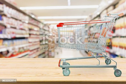 922721264 istock photo Supermarket shopping cart on wood table with grocery store aisle blurred background 963350914