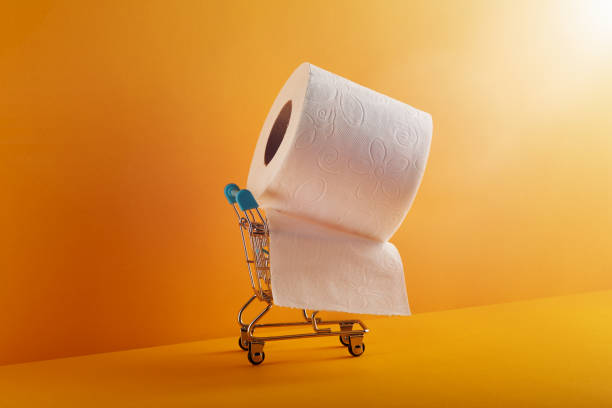 Supermarket shopping cart with huge roll of toilet paper on it over vivid yellow /orange background stock photo