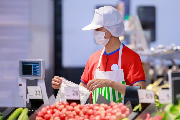 supermarket staff in medical protective mask working at supermarket.covid-19 spreading outbreak - supermarket worker imagens e fotografias de stock