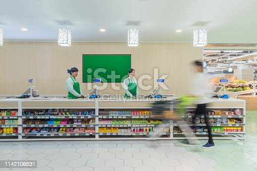 istock Supermarket staff standing at check-out counter 1142106531