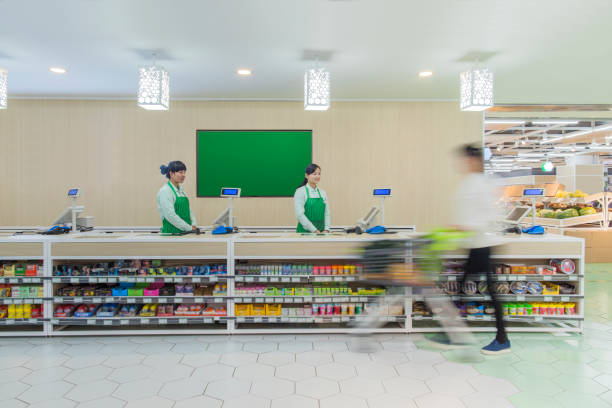 Supermarket staff standing at check-out counter stock photo