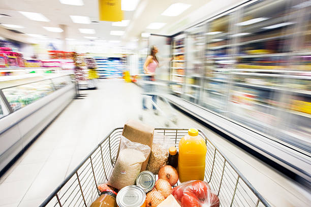 Supermarket trolley moves through fridge area showing motion blur  snack aisle stock pictures, royalty-free photos & images