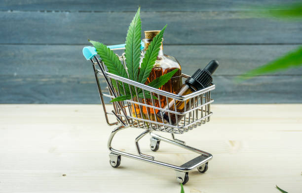 Supermarket trolley with marijuana leafs and medical cannabis oil cbd on wooden backdrop stock photo