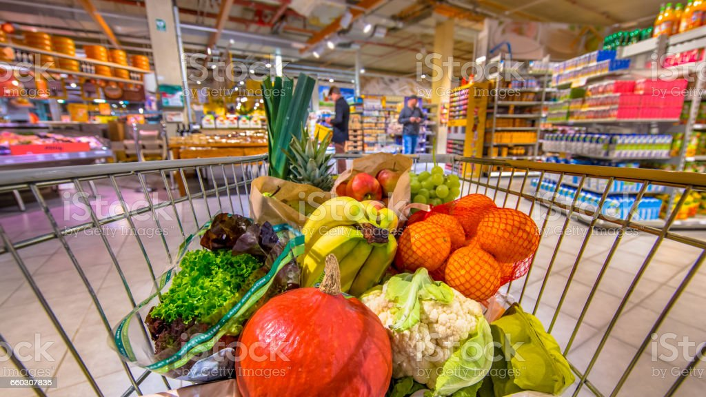 Supermarket trolley with people shopping in background stock photo