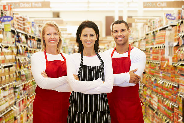 Supermarket Workers Standing In Grocery Aisle Supermarket Workers Standing In Grocery Aisle Smiling To Camera sales clerk stock pictures, royalty-free photos & images