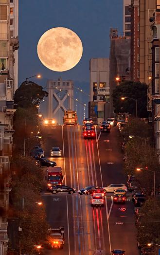 San Francisco California street, bay bridge and supermoon on the background.