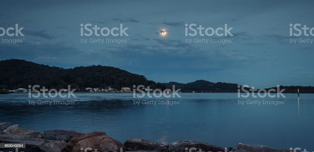 Supermoon rising at the waterfront stock photo