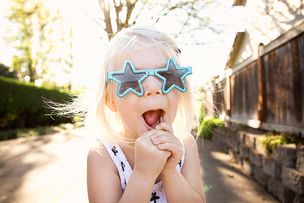 Superstar girl A cute, young girl with blond hair is excited about the moment in her sparkly superstar sunglasses. all star stock pictures, royalty-free photos & images