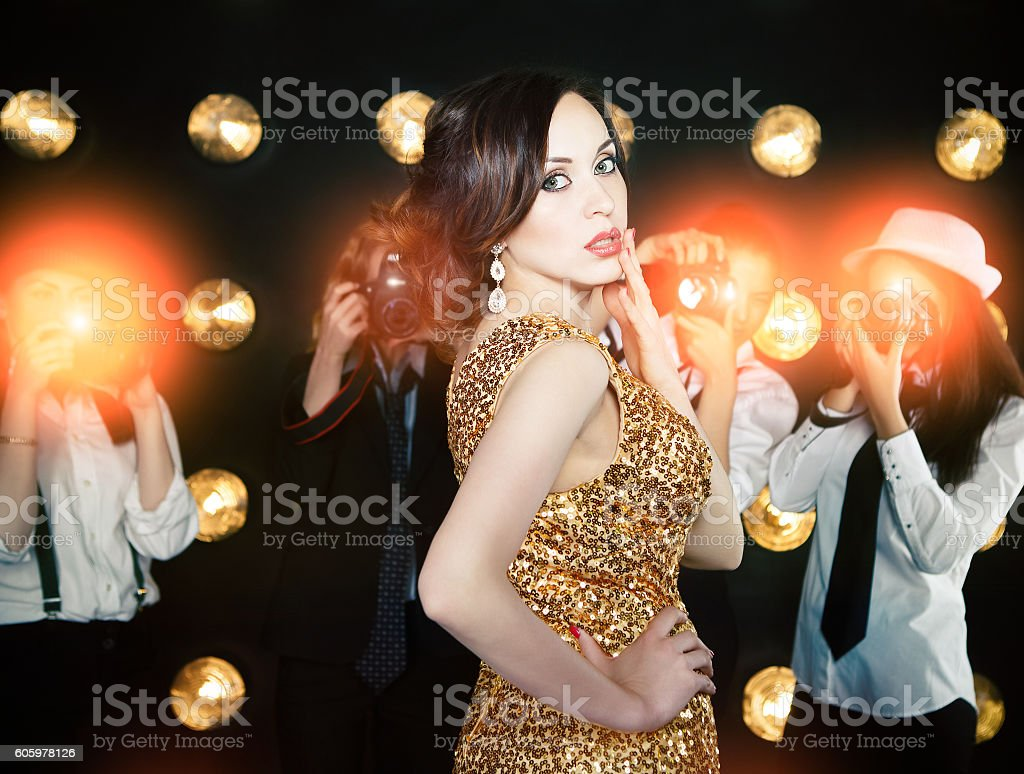 Superstar woman posing to paparazzi stock photo