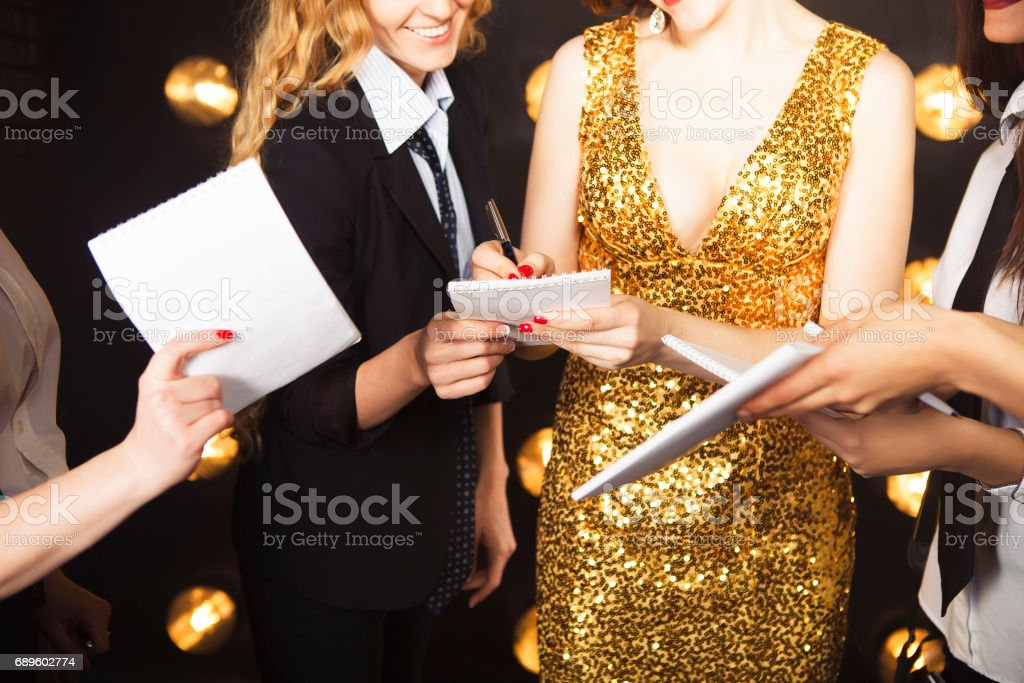 Superstar woman wearing golden shining dress crowded by paparazzi stock photo