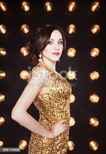 istock Superstar woman wearing golden shining dress posing 938104556