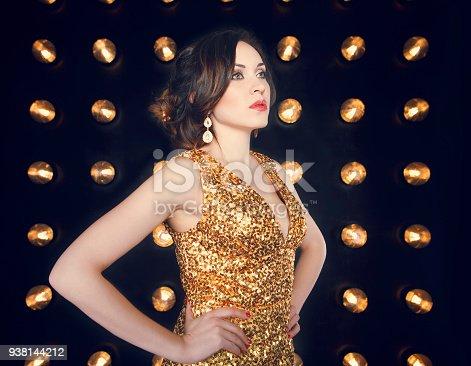 istock Superstar woman wearing golden shining dress posing 938144212