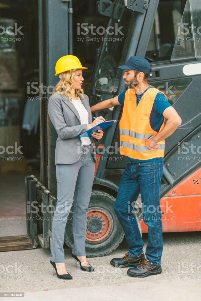 Supervisor and manual worker by the forklift in warehouse Стоковые фото Стоковая фотография
