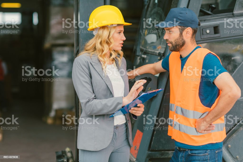 Supervisor and manual worker by the forklift in warehouse foto stock royalty-free