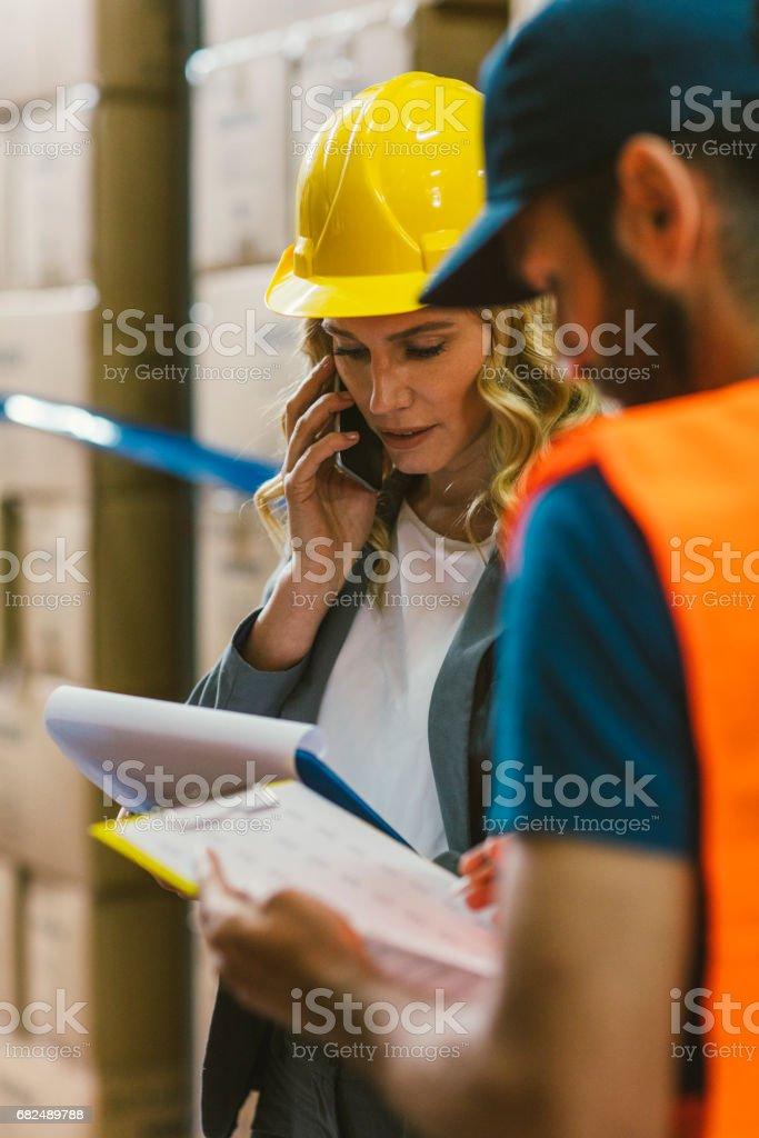 Supervisor and manual worker in warehouse Стоковые фото Стоковая фотография