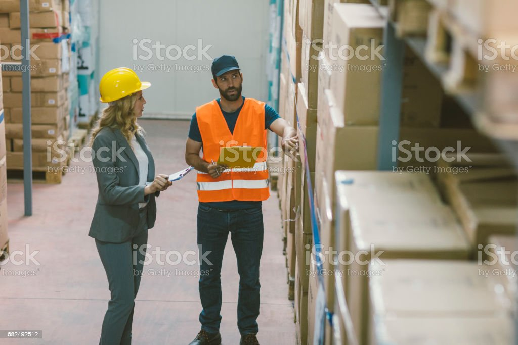 Supervisor and manual worker in warehouse royalty-free stock photo