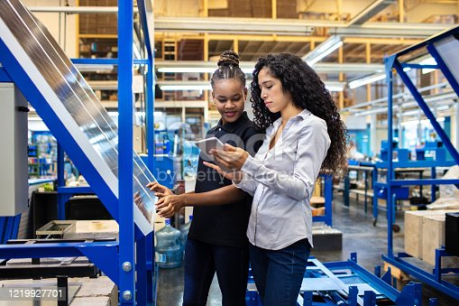 Female engineer showing the production plan to a worker on her digital tablet. Supervisor and female worker looking at digital tablet and discussing work in factory shop floor.