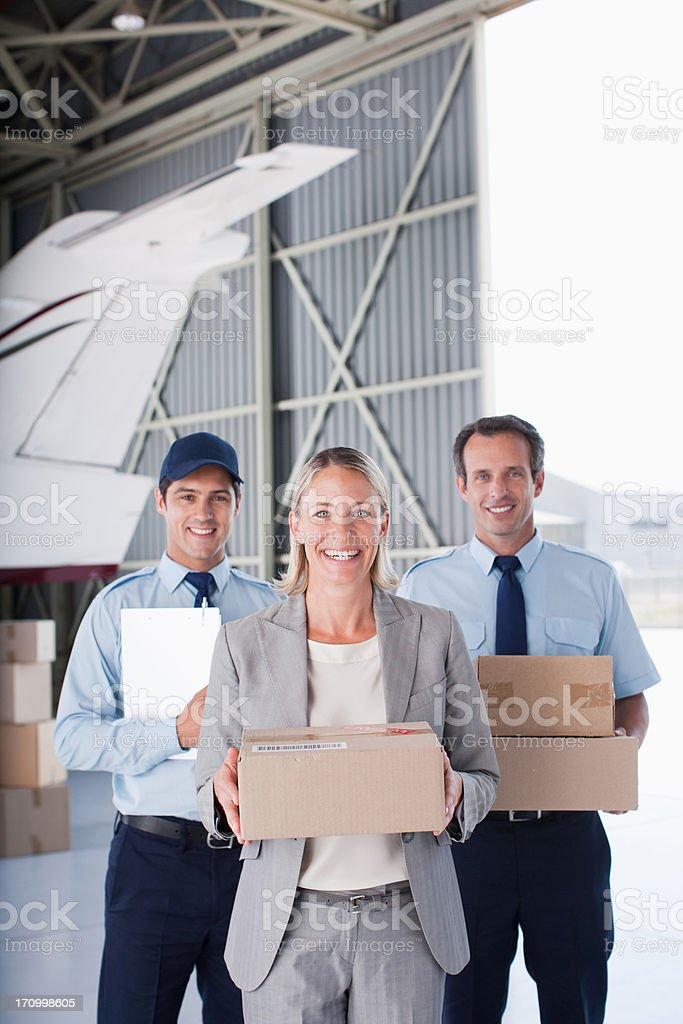 Supervisor and workers holding boxes in hangar royalty-free stock photo