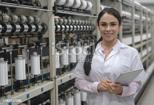 Portrait of a female supervisor checking the operation of a tape factory and smiling while holding a tablet computer – industrial concepts