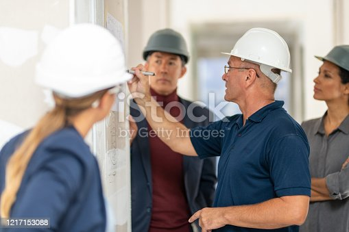 Male supervisor discussing blueprint with architect at construction site.