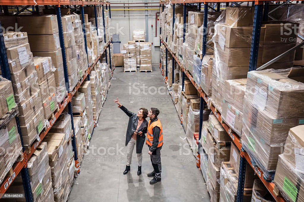 Supervisor discussing with worker in warehouse stock photo