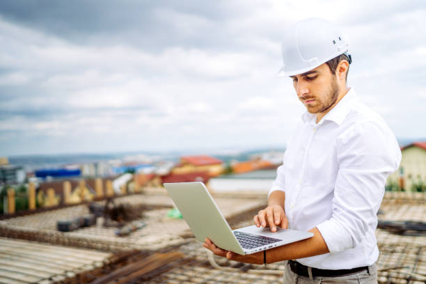 Supervisor engineer using laptop on construction site. Industry details stock photo