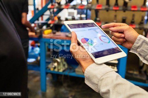 Close-up of a woman explaining pie chart to team over a digital tablet in factory. Factory workers having a meeting at plant shop floor.