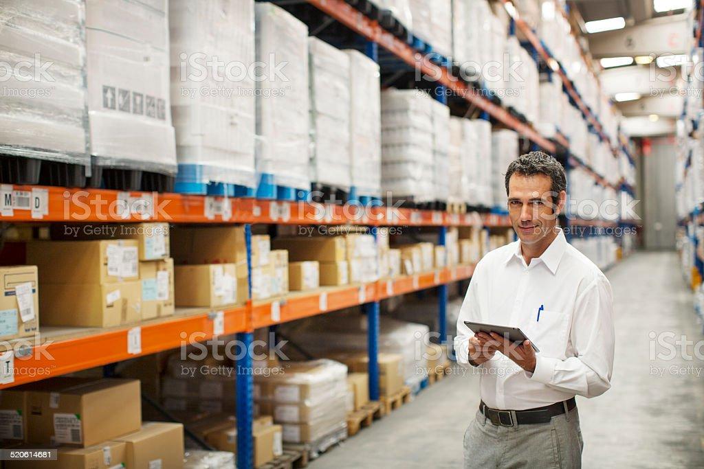 Portrait of confident supervisor holding digital tablet while...