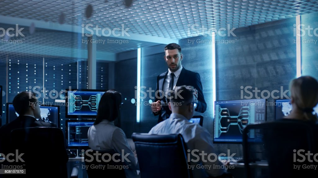 Supervisor Holds Briefing for His Employees in System Control Center Full of Monitors and Servers. Possibly Government Agency Conducts Investigation. - Royalty-free Adult Stock Photo