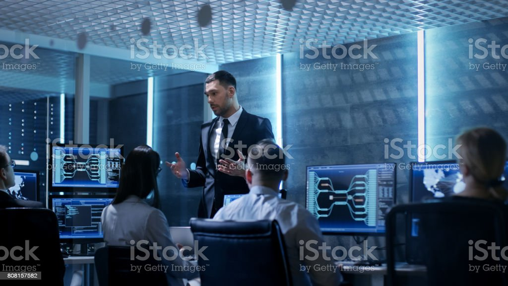 Supervisor Holds Briefing for His Employees in System Control Center Full of Monitors and Servers. Possibly Government Agency Conducts Investigation. Supervisor Holds Briefing for His Employees in System Control Center Full of Monitors and Servers. Possibly Government Agency Conducts Investigation. Adult Stock Photo