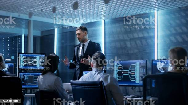 Supervisor Holds Briefing For His Employees In System Control Center Full Of Monitors And Servers Possibly Government Agency Conducts Investigation Stock Photo - Download Image Now
