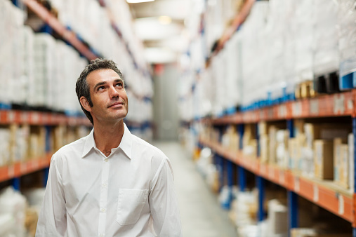 Smiling supervisor looking at stock arranged on shelves in warehouse