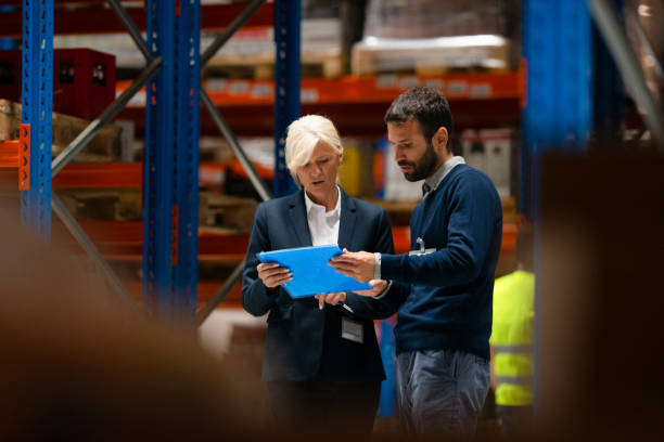 Supervisor taking inventory check with warehouse manager stock photo