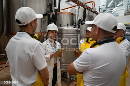 istock Supervisor talking to a group of operators at a brewery 1206641665