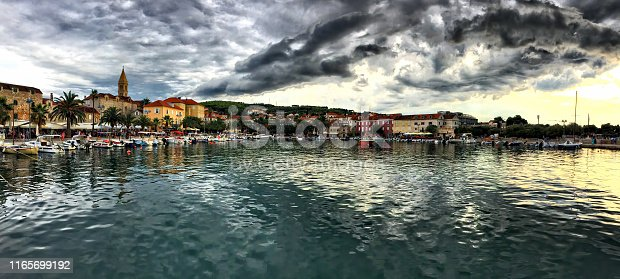 HDR panorama showing Supetar harbor in the afternoon,  famous old town and dramatic cloudscape in the background. Popular touristic destination on Brac island, Dalmatia, Croatia.
