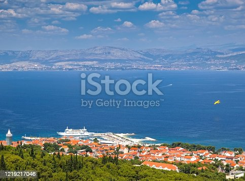 Looking down to idyllic Adriatic coastal town and turquoise sea, Dalmatian coastline in the background, Brac island, Croatia. Supetar is an ideal destination for all those who are looking to benefit from the rich monumental heritage and natural beauties of Central Dalmatia mainland.