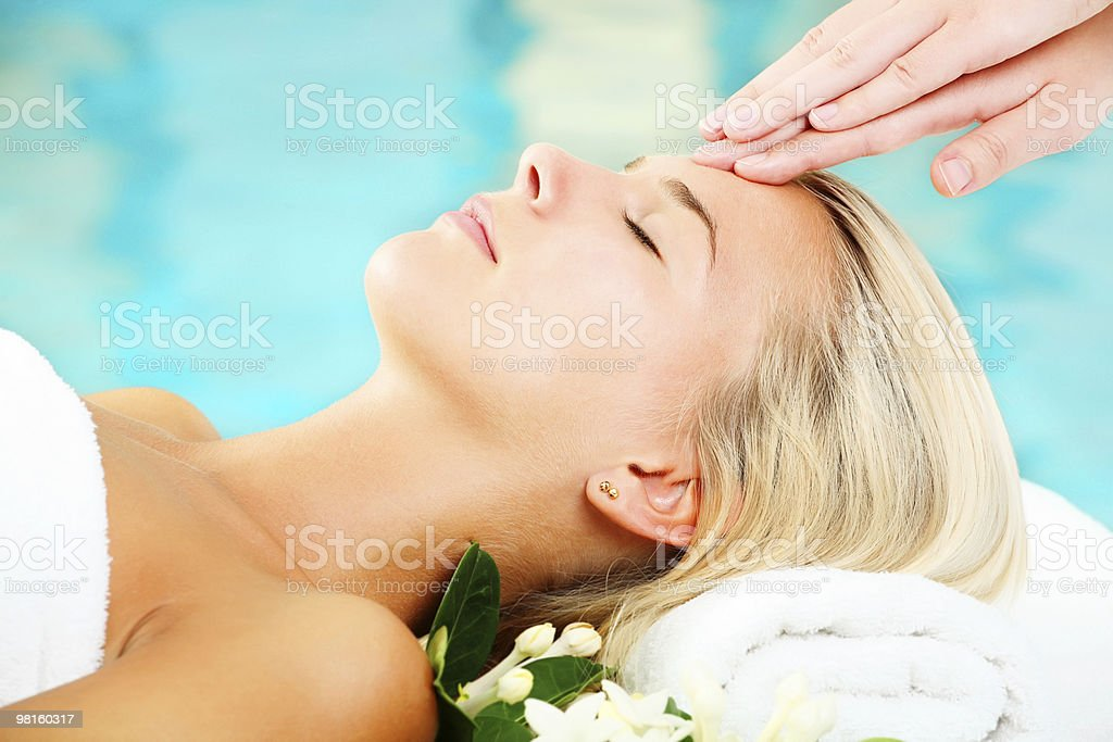 Supine female on a spa bed being gently massaged on temple stock photo