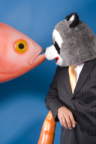 Man in raccoon head with fish and carrot prop.
