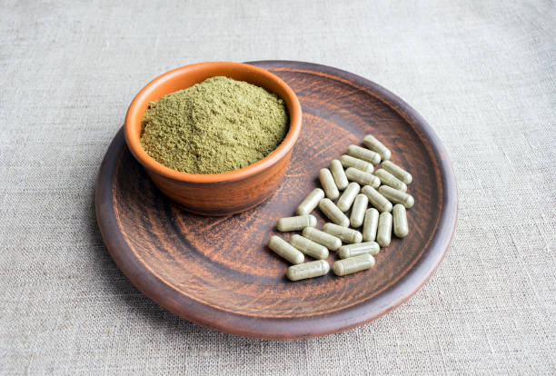 supplement kratom green capsules and powder on brown plate - fda stock photos and pictures