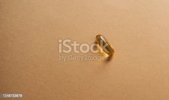 Studio shot of a single gel capsule against a brown background