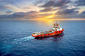 Supply boat offshore oil rig on loading operation with cloudy sky and blue ocean background