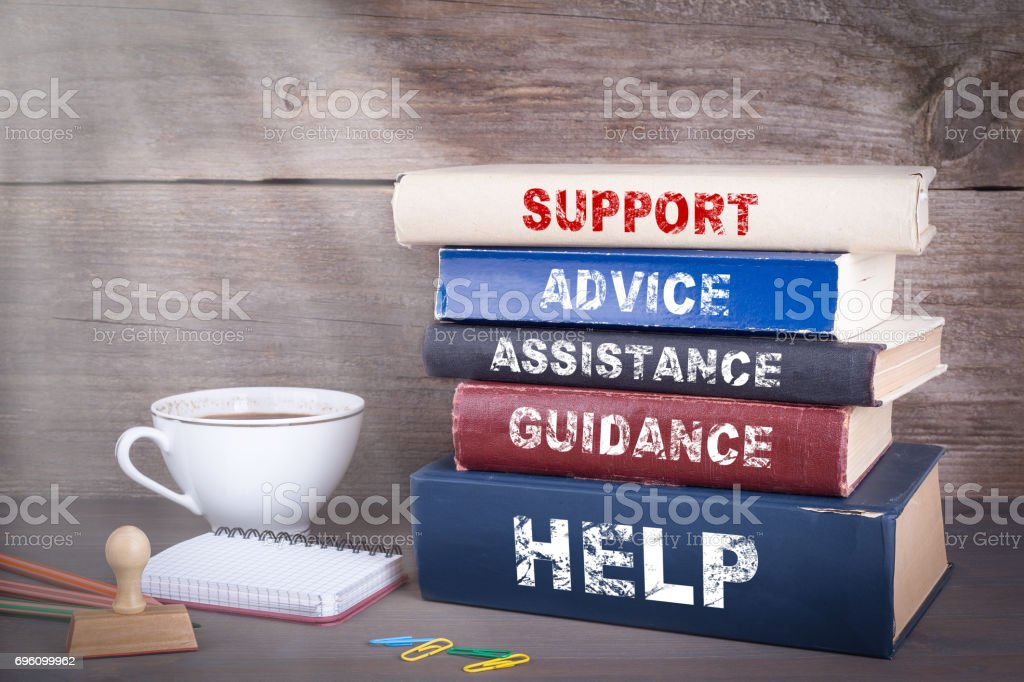 Support concept. Stack of books on wooden desk stock photo