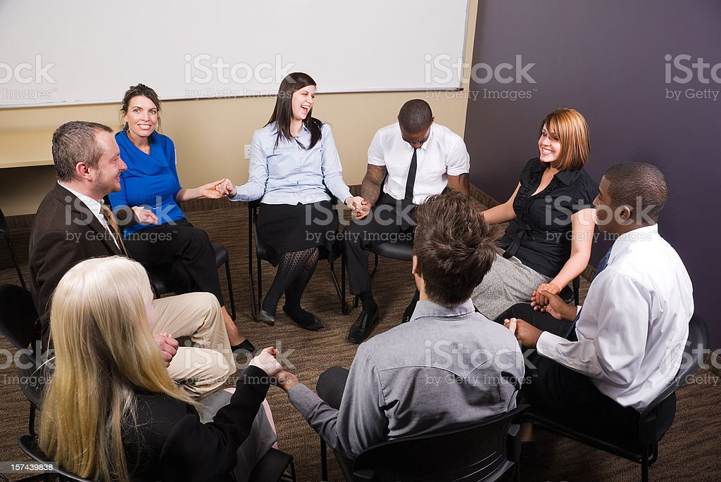 Support group: happy people holding hands in a therapy session stock photo