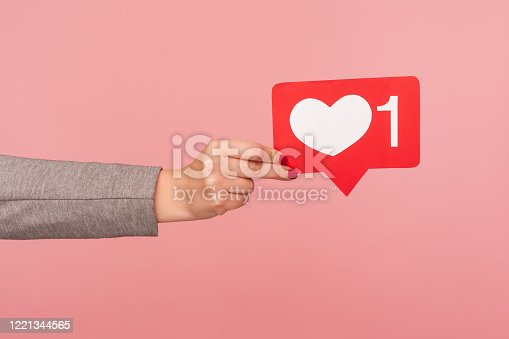 Support interesting web content, push heart button. Closeup of hand holding social media like icon, emoji sign to follow subscribe blog, popular forum. indoor studio shot isolated on pink background