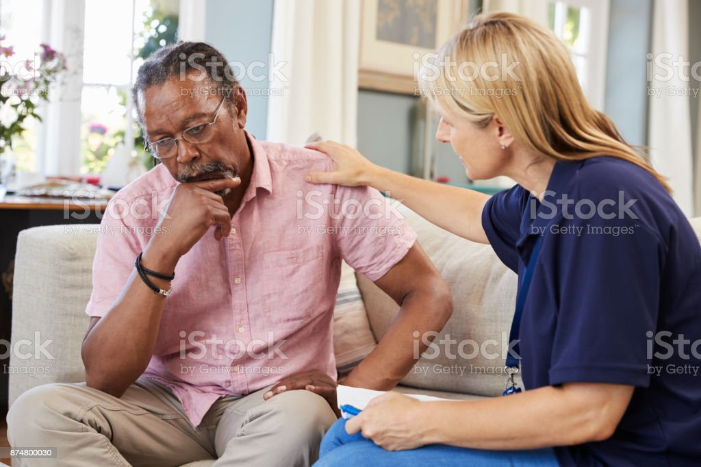 Support Worker Visits Senior Man Suffering With Depression stock photo