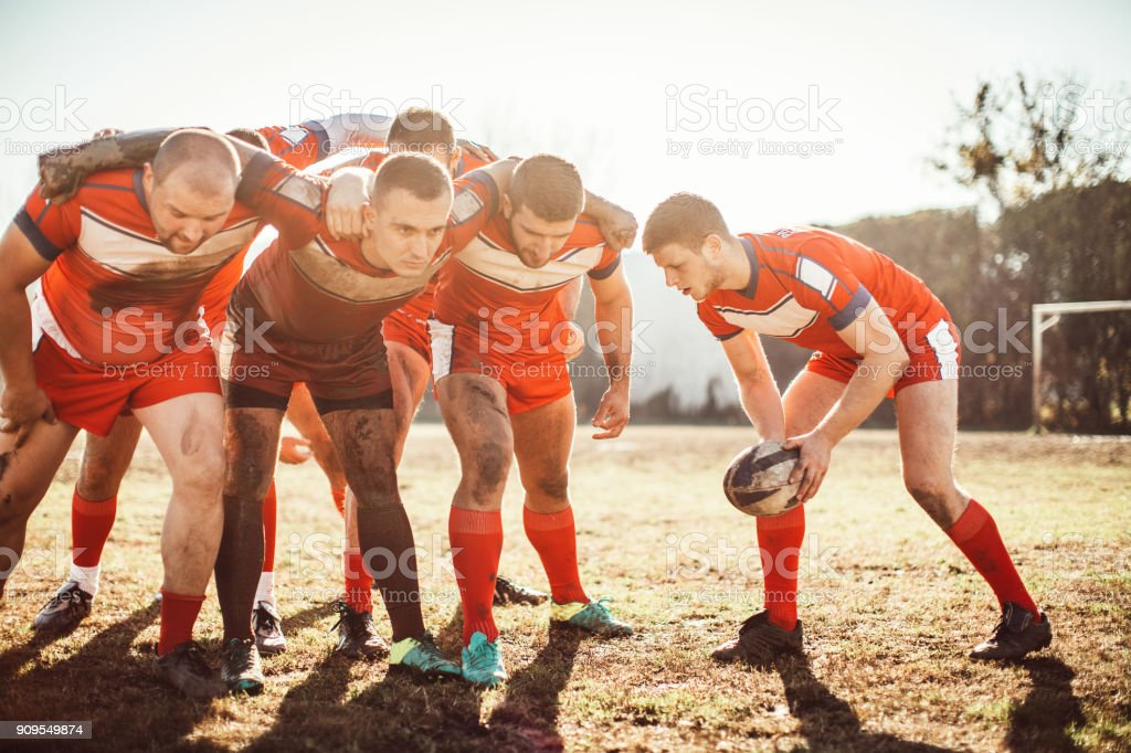 Group of men playing rugby outdoors
