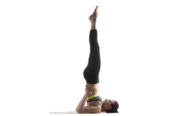 Supported Shoulderstand pose Sporty fit beautiful young woman in sportswear bra and black pants working out, doing Supported Shoulderstand pose, Salamba Sarvangasana, studio full length, isolated, white background shoulder stand stock pictures, royalty-free photos & images