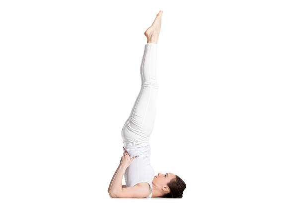 Supported Shoulderstand yoga asana Sporty beautiful young woman in white sportswear doing Supported Shoulderstand exercise, Salamba Sarvangasana, studio full length isolated shot, side view shoulder stand stock pictures, royalty-free photos & images