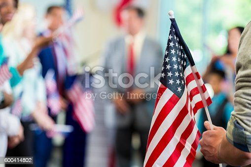 Focus on American flag in a diverse crowd of people. Supporters are cheering for a local candidate at a campaign rally or political town hall meeting.